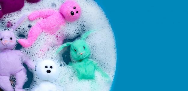 Embeber bonecas de coelho com brinquedos de urso na dissolução da água do detergente antes de lavar. conceito de lavanderia, vista superior