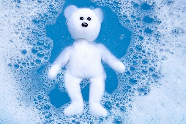 Embeber o urso de brinquedo na dissolução da água do detergente para a roupa antes de lavar. conceito de lavanderia.