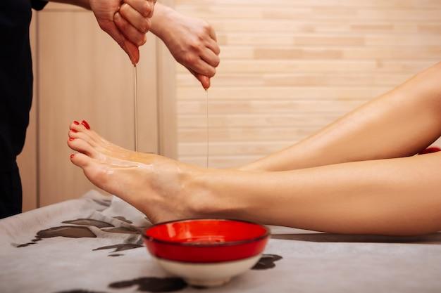 Embeber óleo medicinal. trabalhador profissional em uniforme preto derramando óleo especial nas pernas com pedicure elegante