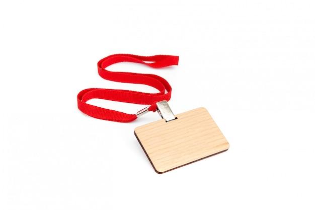 Emblema em branco feito de madeira com laço vermelho.