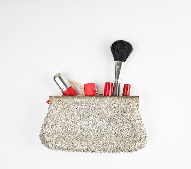 Embreagem de prata aberta e cosméticos caiu do meio