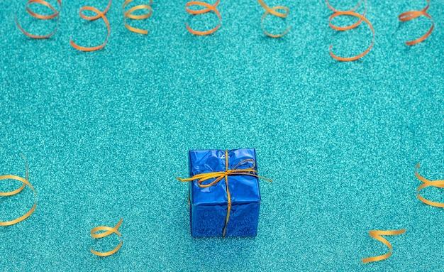 Embrulhado caixa de presente azul clássica com fita de ouro sobre fundo azul com flâmulas de festa brilhantes.
