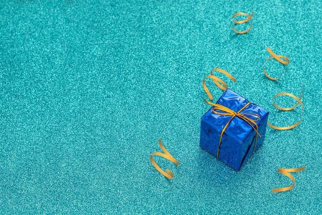 Embrulhado clássico caixa de presente azul com fita de ouro sobre fundo azul com flâmulas de festa brilhantes.