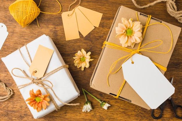 Embrulhado presente amarrado com tag string e bela flor na superfície de madeira
