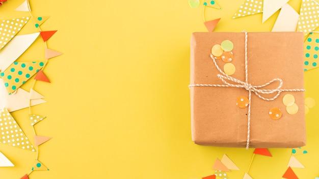 Embrulhado presente de aniversário e bunting em fundo amarelo
