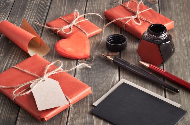 Embrulhado presentes, tinta e canetas para assinar cartões de presente na mesa de madeira