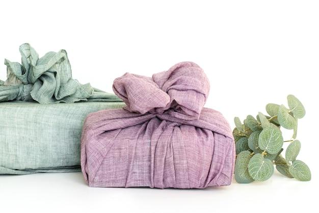 Embrulhar presentes em tecido para o natal no estilo furoshiki. conceito ecológico. faça você mesmo, isolar