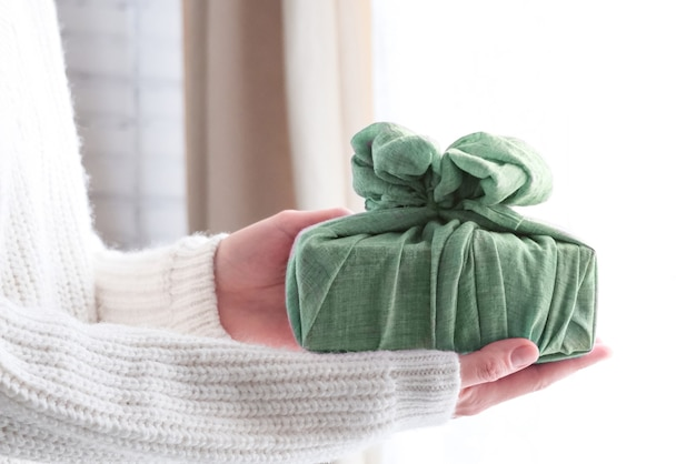 Embrulhar presentes em tecido para o natal no estilo furoshiki. conceito ecológico. faça você mesmo
