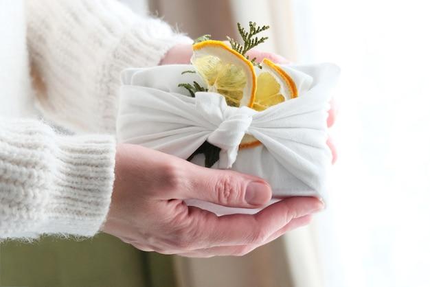 Embrulhar presentes em tecido para o natal no estilo furoshiki. conceito ecológico.