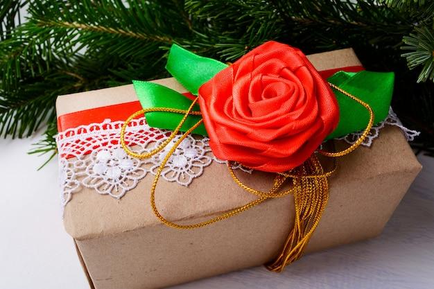 Embrulho de papel kraft de presente de natal com fita dourada e rosa