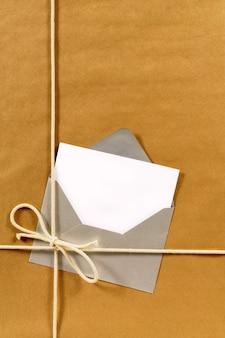 Embrulho de papel pardo com envelope e cartão de mensagem em branco