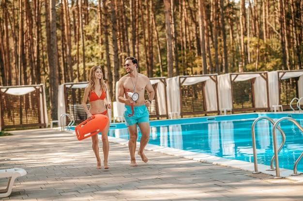Emergência. dois salva-vidas da piscina correndo para o local de emergência