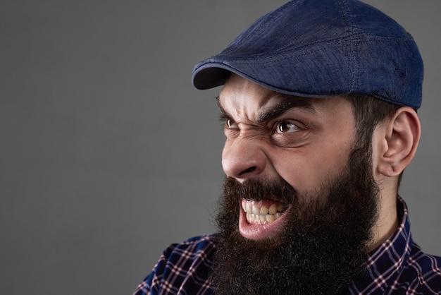 Emoção agressiva com a boca aberta de um homem barbudo em fundo cinza. rosto repulsivo. cara maligno. espaço livre para o texto. pessoa com raiva. feche o retrato do medo.