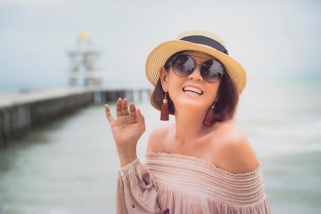 Emoção asiática alegre da felicidade da mulher na praia do mar