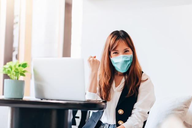 Emoção asiática do sucesso da mulher de negócios - trabalhando em casa o conceito