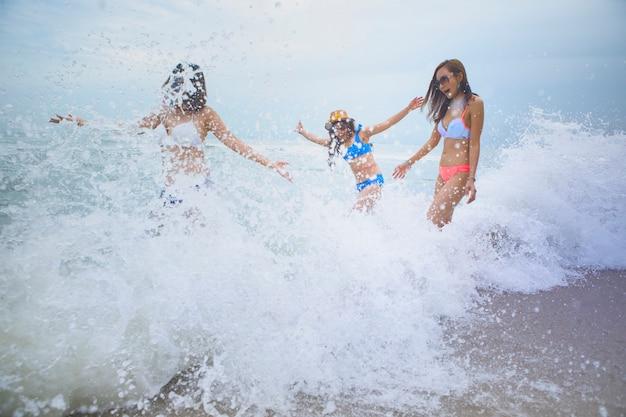 Emoção de felicidade de três mulher com salpicos de onda de praia do mar