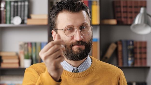 Emoção de gesto de dinheiro de homem. professor barbudo ou empresário com óculos, olhando para a câmera e mostra o gesto com a mão dá-me dinheiro. tiro médio