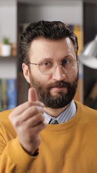 Emoção de gesto de dinheiro de homem. visão vertical do professor barbudo ou empresário com óculos, olhando para a câmera e mostra o gesto com a mão dá-me dinheiro. tiro médio