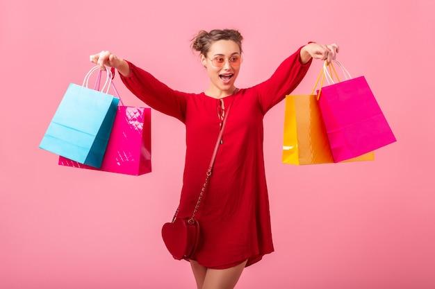 Emoção engraçada feliz atraente, mulher elegante shopaholic em um vestido vermelho da moda segurando sacolas de compras coloridas na parede rosa isolada, venda animada, tendência da moda primavera verão