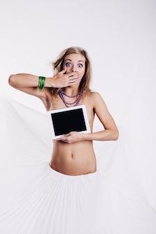 Emoção garota branca com tablet ou computador tablet nas mãos