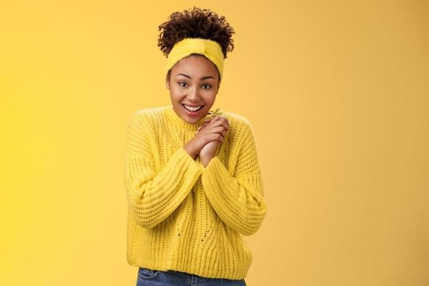 Emocionada fofa encantadora garota afro-americana sorridente cruza os dedos boa sorte, aperte as mãos sorrindo, olhando esperançosamente, câmera rezando boa sorte sonho tornado realidade, acredite, receba notícias positivas