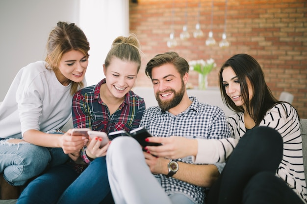 Emocionados jovens amigos com smartphones se divertindo
