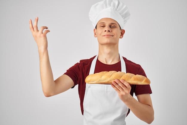 Emocional chef masculino em um pão de avental branco nas mãos de cozimento de cozimento. foto de alta qualidade