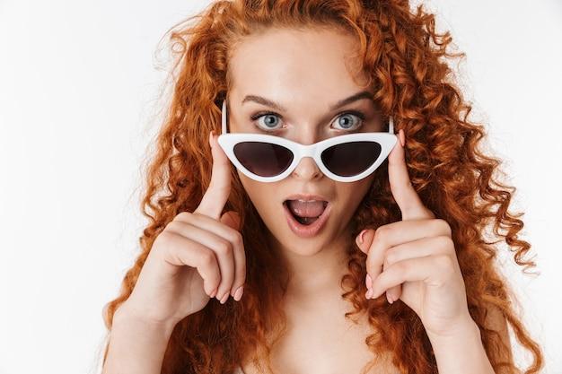 Emocional chocado jovem ruiva encaracolado usando óculos escuros.