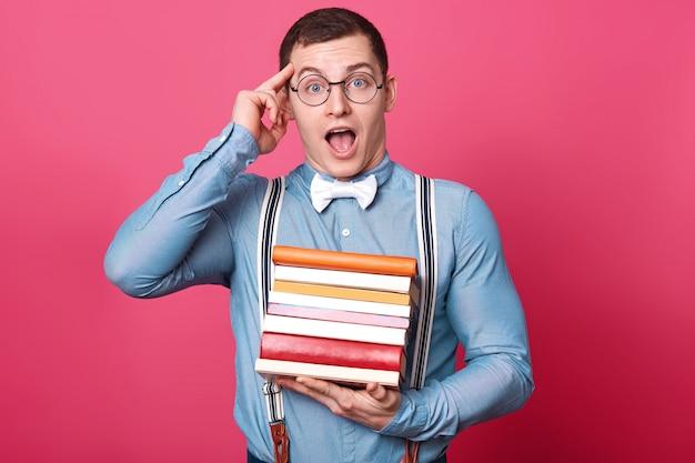 Emocional criativo jovem de cabelos escuros coloca o dedo indicador na têmpora, segura muitos livros em uma mão, abre a boca e os olhos amplamente, mantendo uma idéia incrível em sua mente.