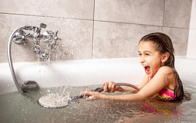 Emocional engraçadinha caucasiana brinca alegremente com água derramando da cabeça do chuveiro durante o banho no banheiro.