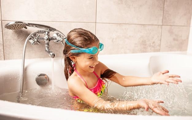 Emocional engraçadinha caucasiana brinca alegremente com água enquanto se banha no banheiro.