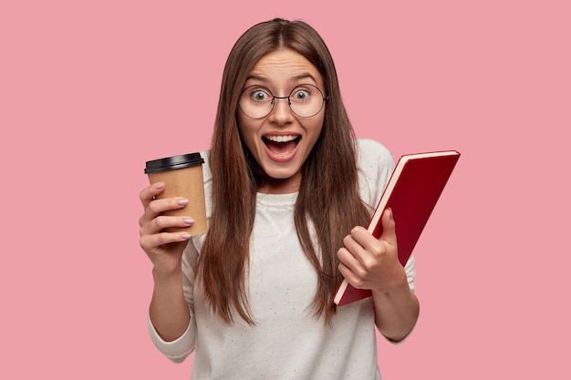 Emocional excitada jovem com cabelos escuros, grita de felicidade, carrega um livro e café para viagem, vestida de blusão branco, sente-se radiante, isolada sobre a parede rosa. conceito de emoções