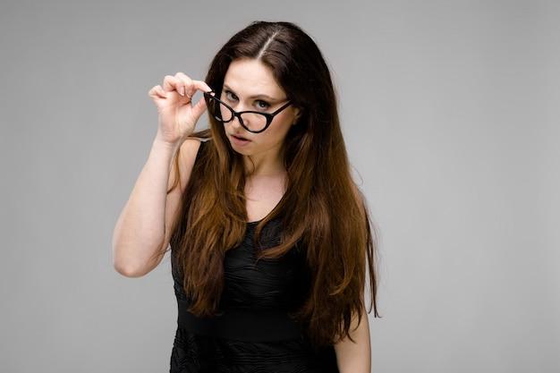 Emocional grave plus size modelo em pé segurando óculos com a mão