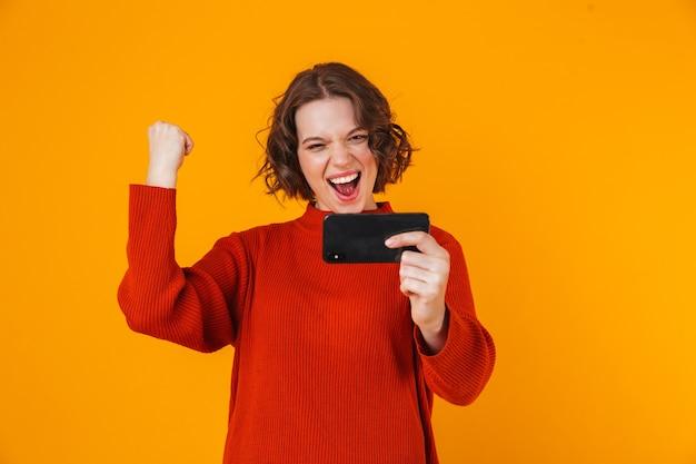 Emocional jovem bonita posando isolada na parede amarela jogar jogos pelo celular fazer gesto de vencedor.