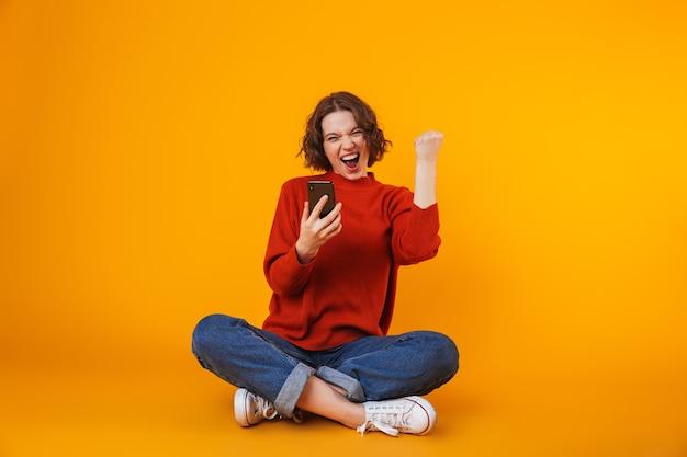 Emocional jovem bonita posando isolada na parede amarela usando telefone celular, fazendo o gesto de vencedor.