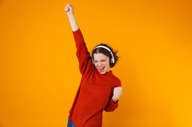 Emocional jovem bonita posando isolado na parede amarela, ouvindo música com fones de ouvido faz gesto de vencedor.