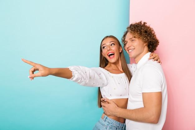 Emocional jovem casal amoroso feliz abraçando posando isolado, olhando para o lado apontando.