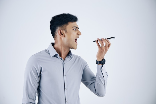 Emocional jovem empresário indiano gritando no microfone do smartphone