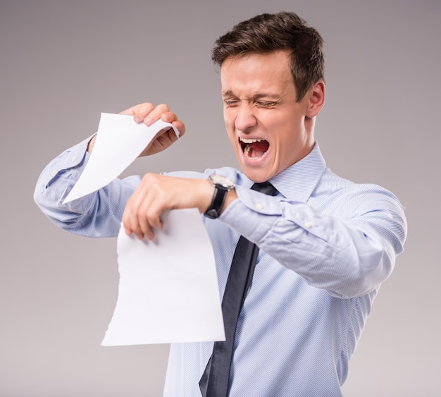 Emocional jovem empresário rasgando o papel.