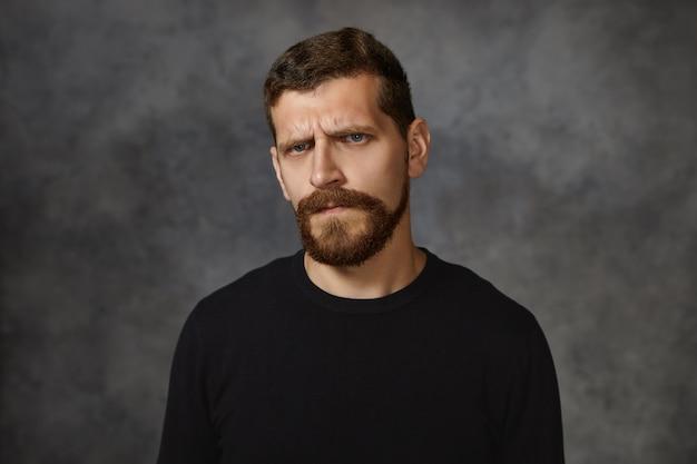 Emocional jovem europeu com barba peluda franzindo a testa, tendo expressão facial desagradável, ficando bravo com seus filhos por mau comportamento, demonstrando aborrecimento e irritação