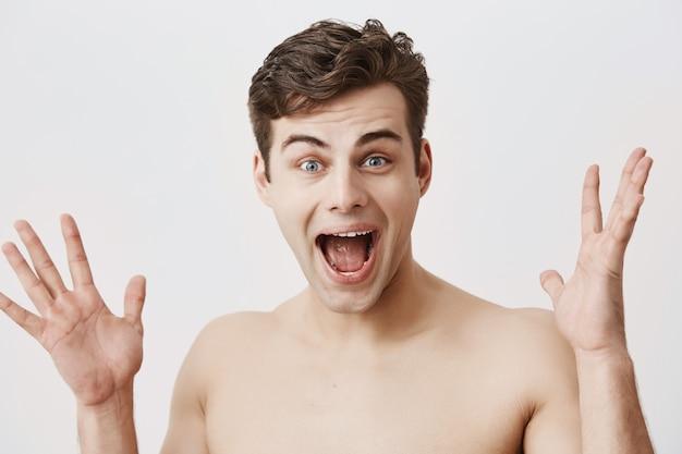 Emocional, sorrindo feliz com o homem de boca aberta tem aparência atraente, penteado na moda, alegrar o sucesso. homem muscular europeu novo que mantém as palmas abertas, sendo surpreendido e feliz.