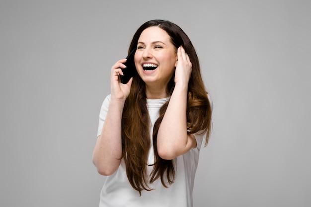 Emocional, sorrindo feliz mais o tamanho do modelo em pé no estúdio, olhando na câmera, falando no telefone com o amigo
