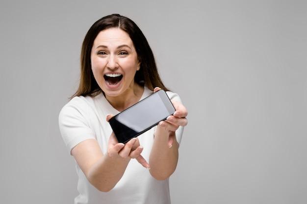 Emocional sorrindo feliz plus tamanho modelo em pé oferecendo telefone celular para um cliente