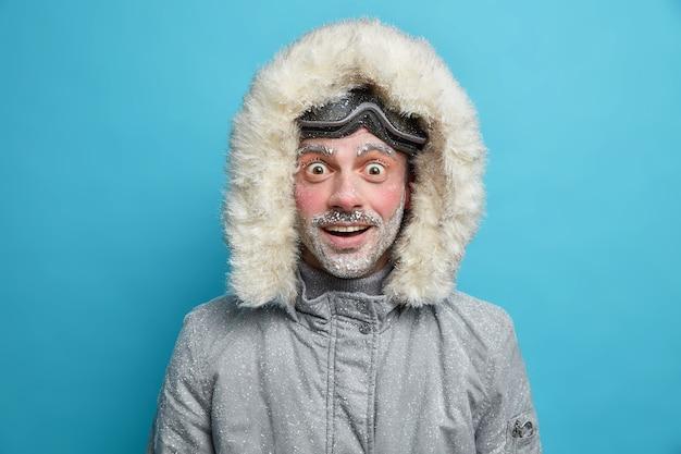 Emocionalmente chocado, alegre, homem usa uma jaqueta de inverno com o rosto vermelho coberto de gelo e não consegue acreditar em notícias surpreendentes