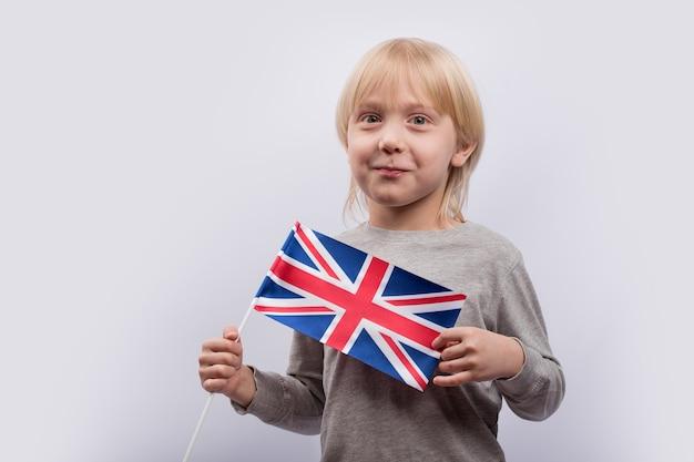 Emocionante rapaz loiro segurando a bandeira do reino unido. aprender inglês para crianças. educação no reino unido.