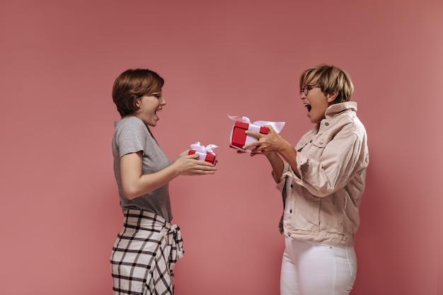 Emocionantes mulheres com cabelo curto e óculos em roupas modernas, segurando caixas de presente vermelhas e regozijando-se no fundo rosa isolado.