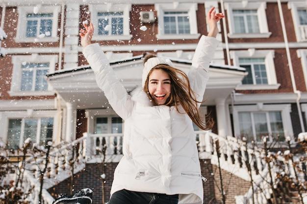 Emoções brilhantes e animadas de uma jovem bonita alegre na rua no inverno. levantando as mãos, felicidade, positividade, alegria, férias de inverno.