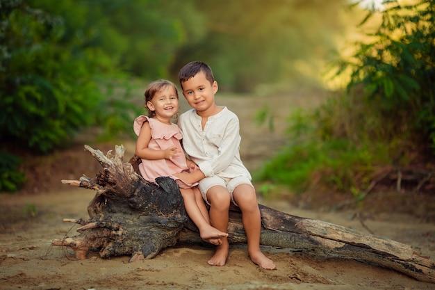 Emoções das crianças. alegre emocional crianças irmão e irmã estão sentados em uma velha árvore seca à beira do rio na areia. eles riem fervorosamente