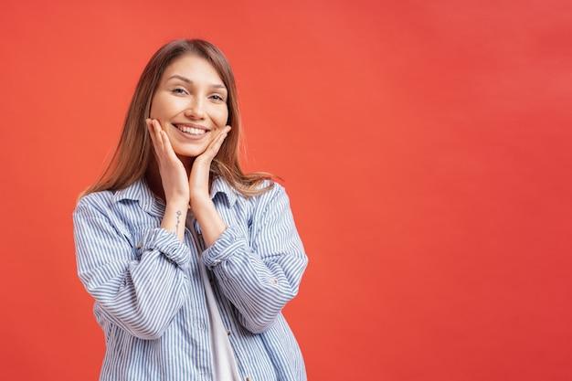 Emoções das pessoas - retrato de menina positiva surpresa sobre parede vermelha