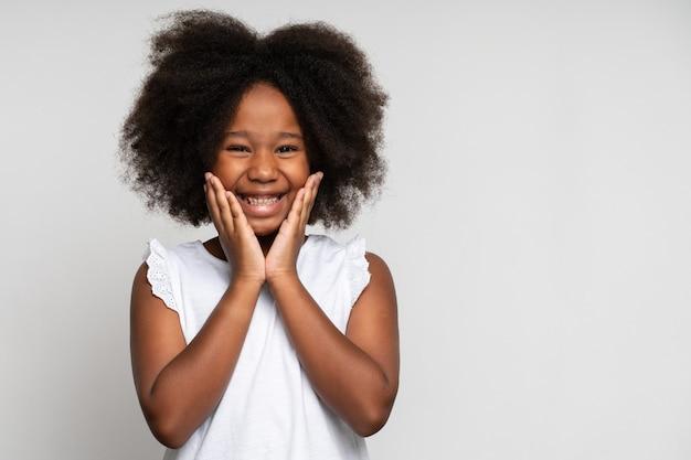 Emoções de criança feliz surpresa. retrato de uma menina adorável de mãos dadas no rosto e sorrindo com espanto, mantendo a boca bem aberta, a expressão chocada. foto de estúdio isolada em fundo branco